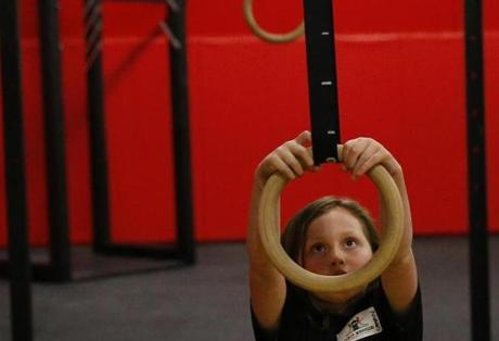 Camryn Knoblauch, 8, of North Andover swung on a ring during an American Ninja Warrior training course at Gymja in Danvers.